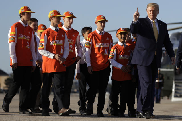 President Donald Trump walks to board Air Force One with Louisiana's Eastbank Little League team on Friday at Andrews Air Force Base. Trump was heading to a campaign rally in Lake Charles, La. (AP)