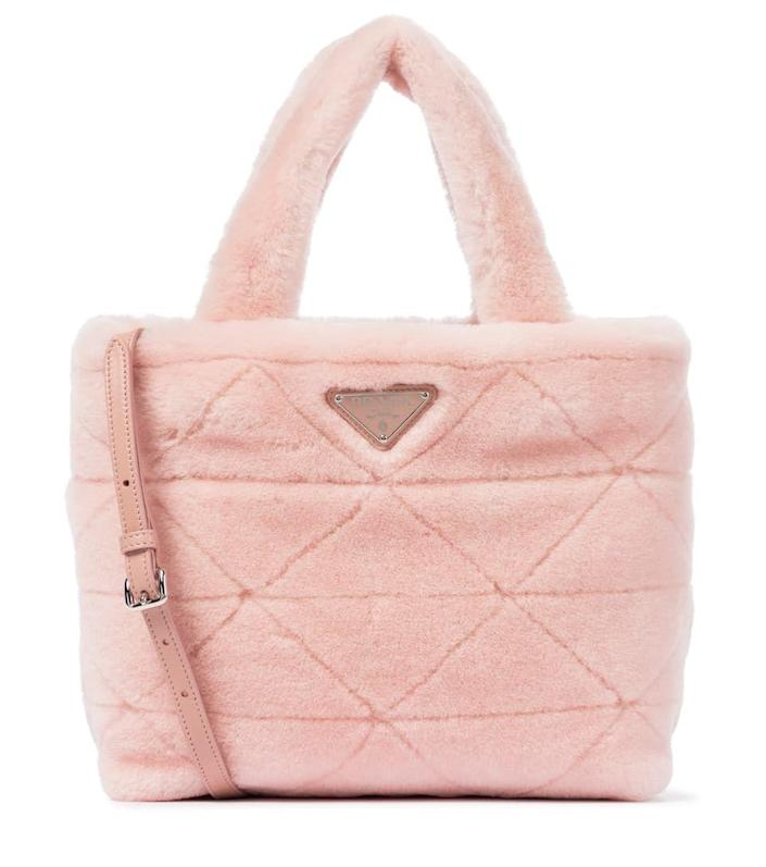 """<p><strong>Prada</strong></p><p>mytheresa.com</p><p><strong>1950.00</strong></p><p><a href=""""https://click.linksynergy.com/deeplink?id=6Km1lFswsiY&mid=43172&murl=https%3A%2F%2Fwww.mytheresa.com%2Feuro_en%2Fprada-shearling-tote-1738986.html%3Fcatref%3Dcategory"""" rel=""""nofollow noopener"""" target=""""_blank"""" data-ylk=""""slk:Shop Now"""" class=""""link rapid-noclick-resp"""">Shop Now</a></p><p>A great way to ease your wardrobe into fall is to adopt a furry friend you can bring everywhere with you. Begin by pairing it with a summer dress, and as it gets colder, it will look just as good with your favorite coat. </p>"""