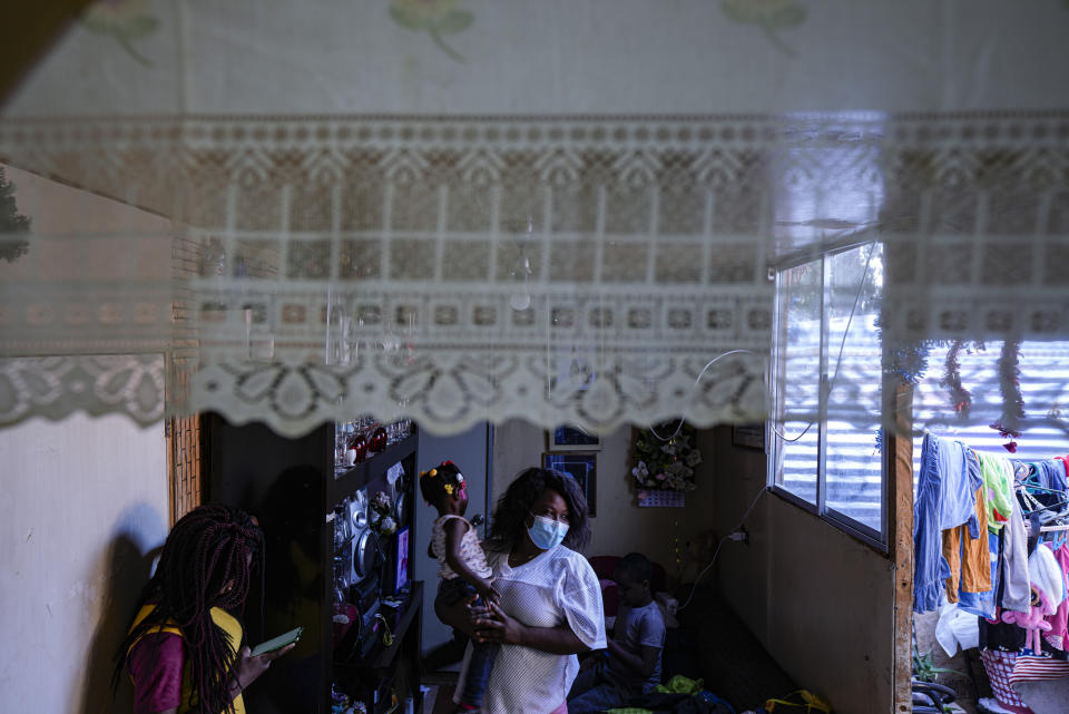 """Magdaline Alfred, a Haitian with permanent residence in Chile, carries her Chilean-born, two-year-old daughter Cataleya next to her other daughter Develine, born in the Dominican Republic, inside their home in Santiago's Dignidad camp, in Chile, Thursday, Sept. 30, 2021. """"It makes me very sad because many left (for the U.S.) with their children who were born here ... and now they are deporting (to Haiti) Haitians with Chilean children,"""" she said of other Haitian migrants in Chile. (AP Photo/Esteban Felix)"""