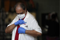 """A man wearing gloves and a mask to protect against COVID-19 affixes an """"I voted"""" sticker to his shirt as he leaves a polling place at Indian Creek Fire Station #4 in Miami Beach, Fla., on Election Day, Tuesday, Nov. 3, 2020.(AP Photo/Rebecca Blackwell)"""