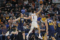Phoenix Suns guard Devin Booker (1) lays up the ball as Utah Jazz guard Joe Ingles (2) defends in the first half during an NBA basketball game Monday, Feb. 24, 2020, in Salt Lake City. (AP Photo/Rick Bowmer)