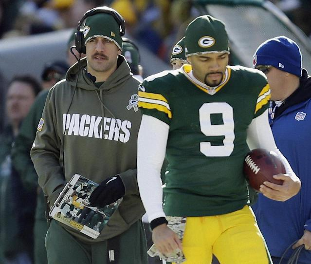 Green Bay Packers' Aaron Rodgers is seen on the sidelines with Seneca Wallace (9) during the first half of an NFL football game against the Philadelphia Eagles Sunday, Nov. 10, 2013, in Green Bay, Wis. (AP Photo/Mike Roemer)
