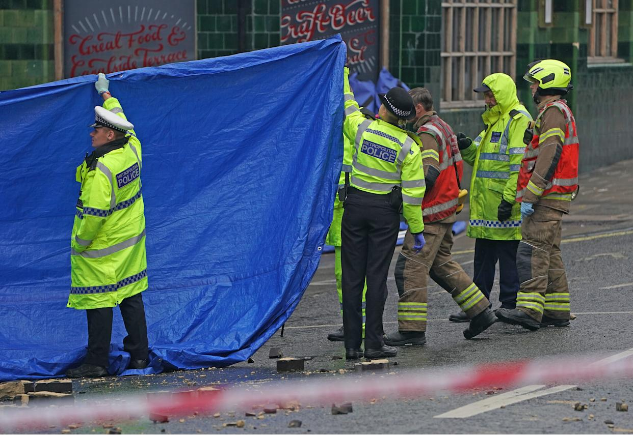 Emergency services at the scene on the Great Western Road, Notting Hill, west London, where three people have died after a vehicle collided with a residential block after a vehicle collided with a residential block. Picture date: Tuesday September 14, 2021.
