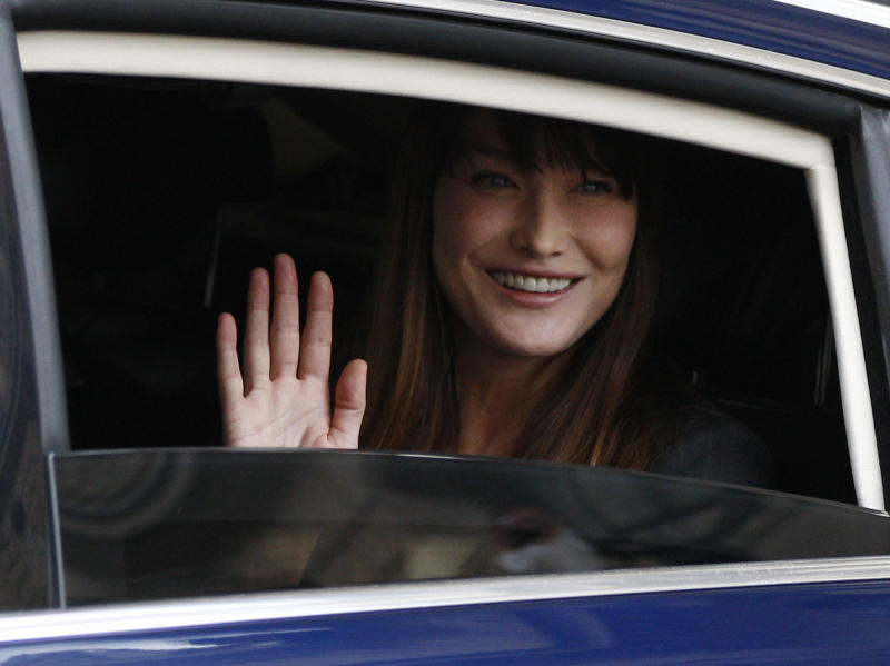 """FILE - In this May 15, 2012 file photo, Carla Bruni-Sarkozy, wife of outgoing President Nicolas Sarkozy, waves from a car as they leave the Elysee Palace after the presidential handover ceremony.  Carla Bruni-Sarkozy has said Monday, Nov. 26, 2012 she supports the French Socialist's plans for gay marriage, and disagrees with her Conservative husband Nicolas Sarkozy. In an interview in the December issue of Paris Vogue, the 44-year-old former supermodel and singer said: """"I'm rather in favor because I have a lot of friends - men and women -who are in this situation and I see nothing unstable or perverse in homoparental families.""""  (AP Photo/Michel Euler, File)"""