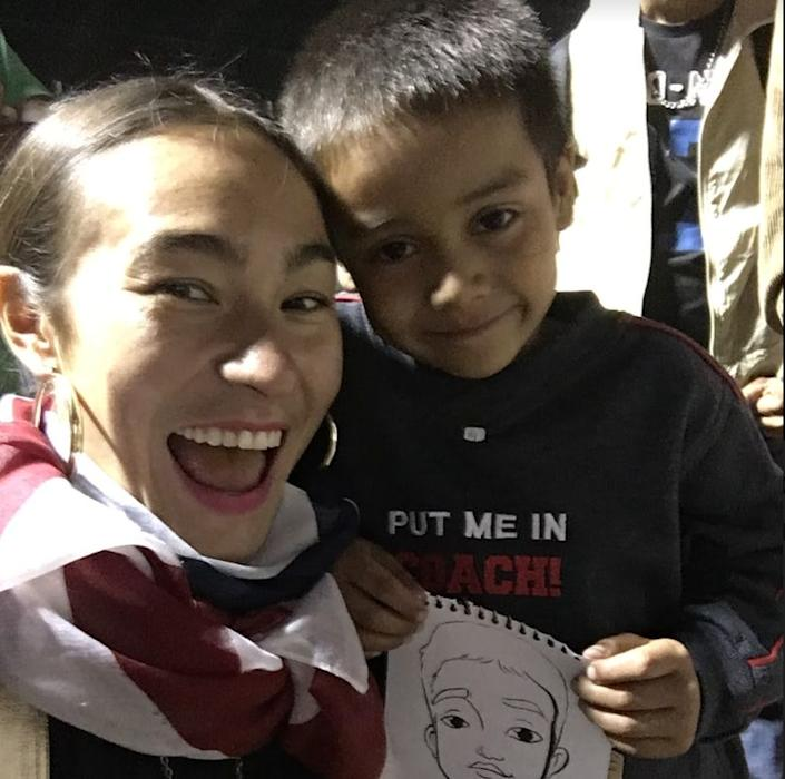 Artist Scarlett Baily inMexico City with a child in the migrant caravan. (Photo: )