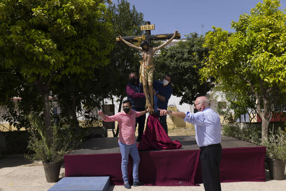 After a Palm Sunday mass, members of a Catholic brotherhood place the figure of Jesus into the church of Nuestra Senora de la Candelaria in Seville, southern Spain, Sunday, March 28, 2021. Few Catholics in devout southern Spain would have imagined an April without the pomp and ceremony of Holy Week processions. With the coronavirus pandemic unremitting, they will miss them for a second year. (AP Photo/Laura Leon)