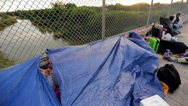 Maidelen Gonzales, an immigrant from Honduras seeking asylum in the United States, waits under a tarp on the Brownsville and Matamoros International Bridge, Friday, Nov. 2, 2018, in Matamoros, Mexico. (The Associated Press)