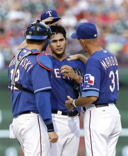 Texas Rangers pitching coach Mike Maddux (31) tries to settle down starting pitcher Marin Perez as catcher A.J. Pierzynski (12) joins them at the mound during the second inning of a baseball game against the Baltimore Orioles on Sunday, July 21, 2013, in Arlington, Texas. (AP Photo/LM Otero)