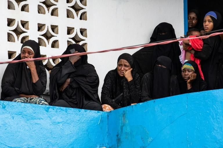 Women watch on from a balcony as bodies are taken away from the site of the fire on Thursday (AFP Photo/Carielle DOE)