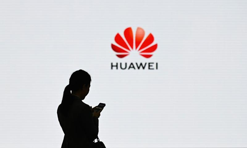 A silhouette of a woman on her phone in front of the Huawei logo