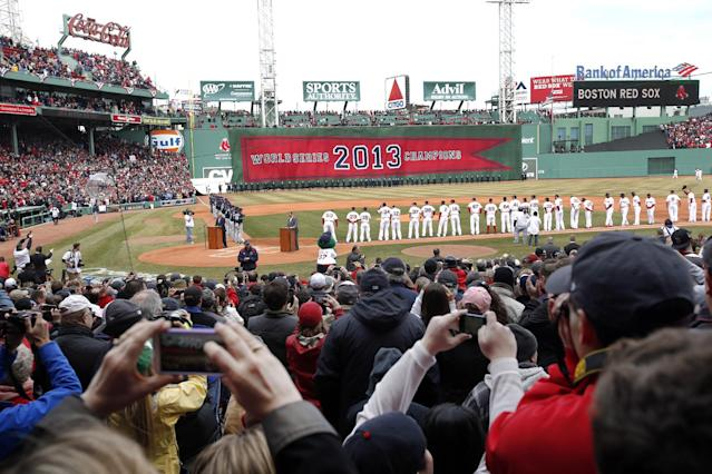 Fans take pictures as players line the field at Fenway Park in Boston, Friday, April 4, 2014, during opening day ceremonies prior to a baseball game between the Boston Red Sox and the Milwaukee Brewers. (AP Photo/Elise Amendola)
