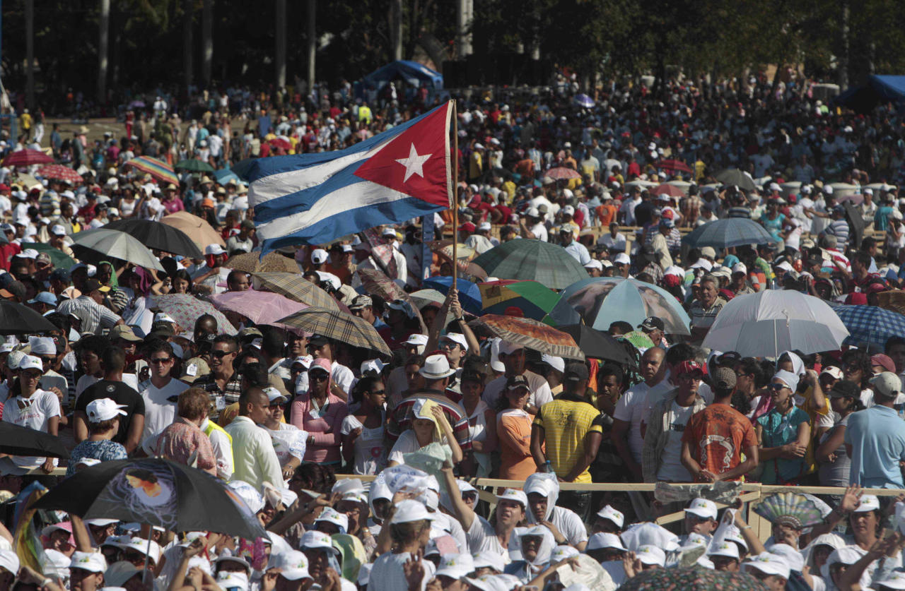 People, among them a man waving a Cuban flag, wait for the arrival of Pope Benedict XVI at the Antonio Maceo Revolution Square where he will celebrate Mass in Santiago de Cuba, Cuba, Monday, March, 26, 2012. (AP Photo/Esteban Felix)