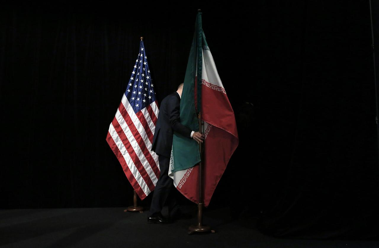 A staff member removes the Iranian flag from the stage after a group picture with foreign ministers and representatives of Unites States, Iran, China, Russia, Britain, Germany, France and the European Union during the Iran nuclear talks at the Vienna International Center in Vienna, Austria Tuesday July 14, 2015. After 18 days of intense and often fractious negotiation, world powers and Iran struck a landmark deal Tuesday to curb Iran's nuclear program in exchange for billions of dollars in relief from international sanctions — an agreement designed to avert the threat of a nuclear-armed Iran and another U.S. military intervention in the Muslim world. (Carlos Barria, Pool Photo via AP)
