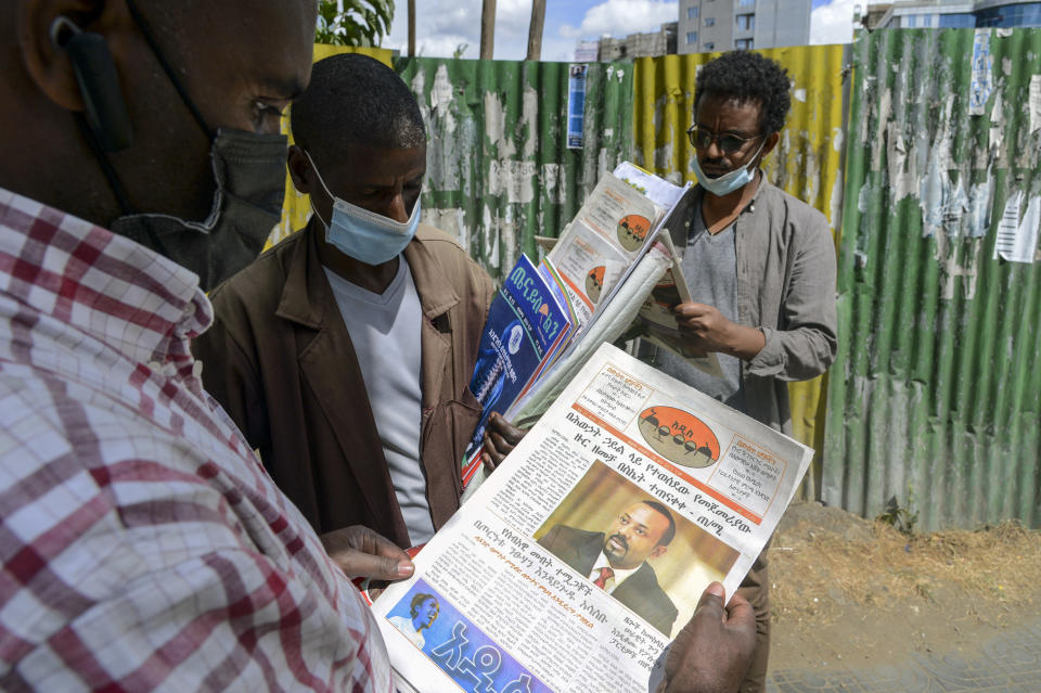Ethiopians read newspapers and magazines reporting on the current military confrontation in the country, one of which shows a photograph of Prime Minister Abiy Ahmed, on a street in the capital Addis Ababa, Ethiopia Saturday, Nov. 7, 2020. Ethiopia moved Saturday to replace the leadership of the country's defiant northern Tigray region, where deadly clashes between regional and federal government forces are fueling fears the major African power is sliding into civil war. (AP Photo/Samuel Habtab)