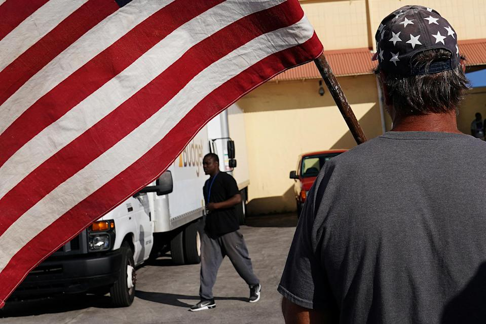 A man holding a flag verbally insults another man outside Broward County election offices during a ballot recount in Lauderhill, Fla. (Photo: Carlo Allegri/Reuters)