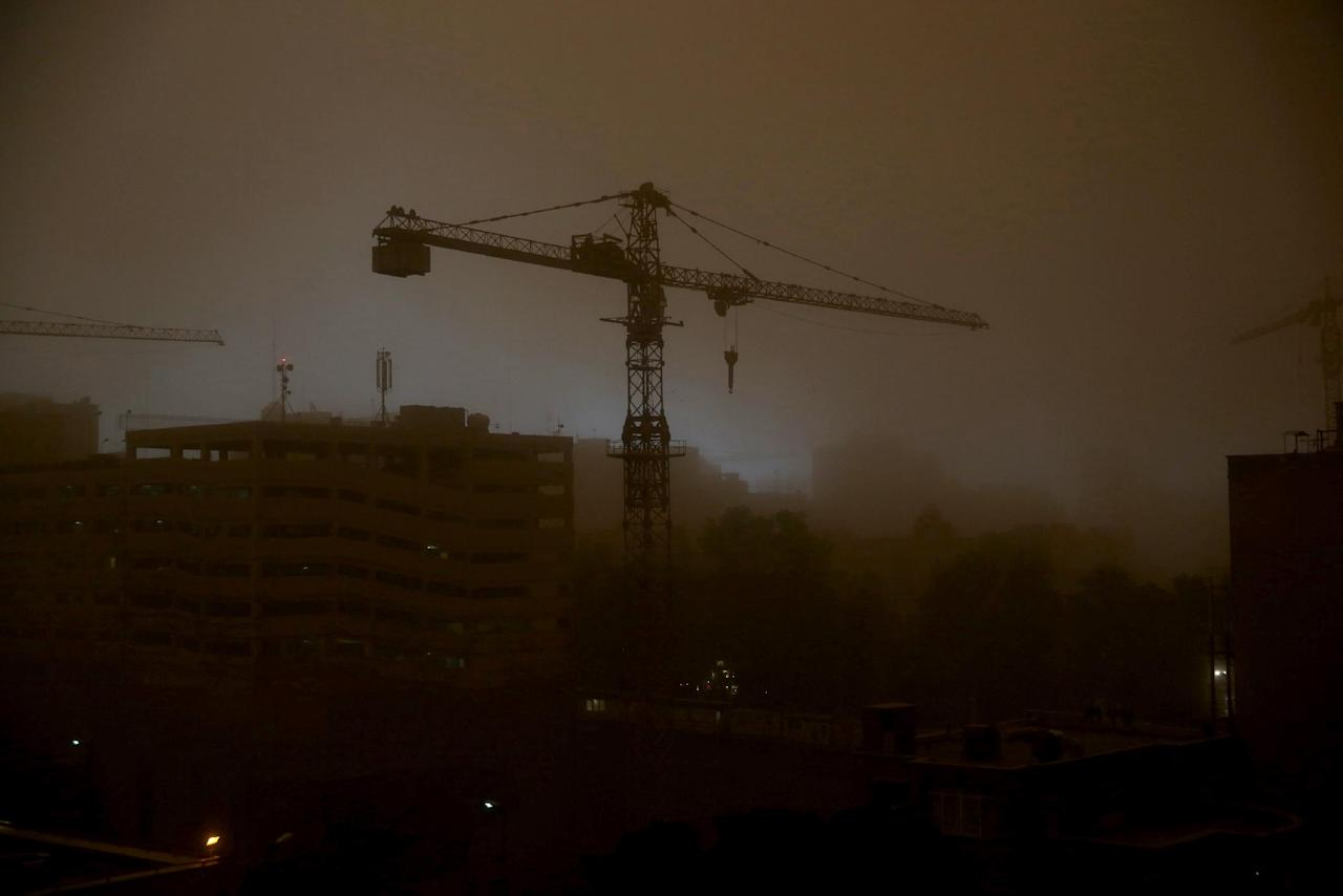 A tower crane is is enveloped in dust in Tehran, Iran, Monday, June 2, 2014, while a flash dust storm hits the Iranian capital. Iran's state TV is reporting that at least two people have been killed and 30 others injured after a heavy dust storm hit the capital Tehran with a speed of 110 kilometers per hour. (AP Photo/Ebrahim Noroozi)
