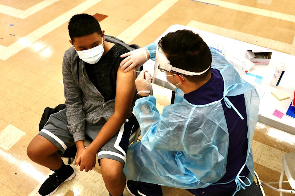 A student receives a dose of the COVID-19 vaccine.