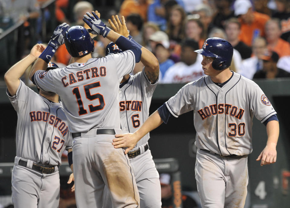 Houston Astros' Jason Castro (15) is greeted by teammates, from left to right, Jose Altuve, Jonathan Villar and Matt Dominguez after they scored on his grand slam in the fourth inning of a baseball game against the Baltimore Orioles, Wednesday, July 31, 2013, in Baltimore. (AP Photo/Gail Burton)
