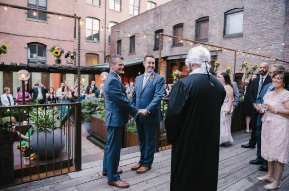 """""""Mark and Steven surprised their guests with an unannounced ceremony where the officiant was dressed up like a judge! The ceremony was a beautiful mix of fun and touching moments."""" --&nbsp;<i>Williamsburg Photo Studios&nbsp;</i>"""
