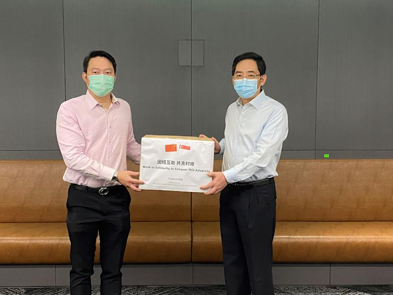 Senior Minister of State for Health and Transport Lam Pin Min (left) receives a donation of face masks from China ambassador Hong Xiaoyong. (PHOTO: Ministry of Health)