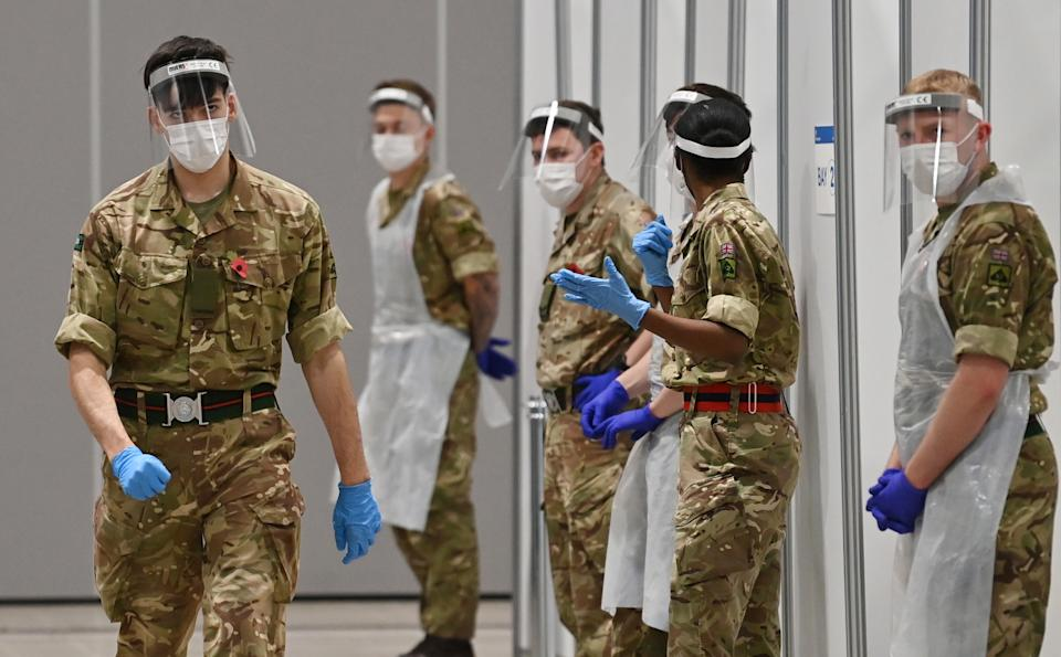 Soldiers wearing full PPE (personal protective equipment) in the form of face shields, gloves, face masks and bibs wait to assist covid testing at a coronavirus rapid testing centre in the Liverpool exhibition centre in Liverpool, north-west England on November 11, 2020, during a city-wide mass testing pilot operation. - Liverpool on November 6 began England's first city-wide trial of coronavirus testing in an attempt to prevent hospitals becoming overwhelmed during the country's second wave of the pandemic. All of the northwestern city's 500,000 residents as well as people working there will be offered repeat tests, even if asymptomatic, under the pilot trial, which will initially run for two weeks. (Photo by Paul ELLIS / AFP) (Photo by PAUL ELLIS/AFP via Getty Images)