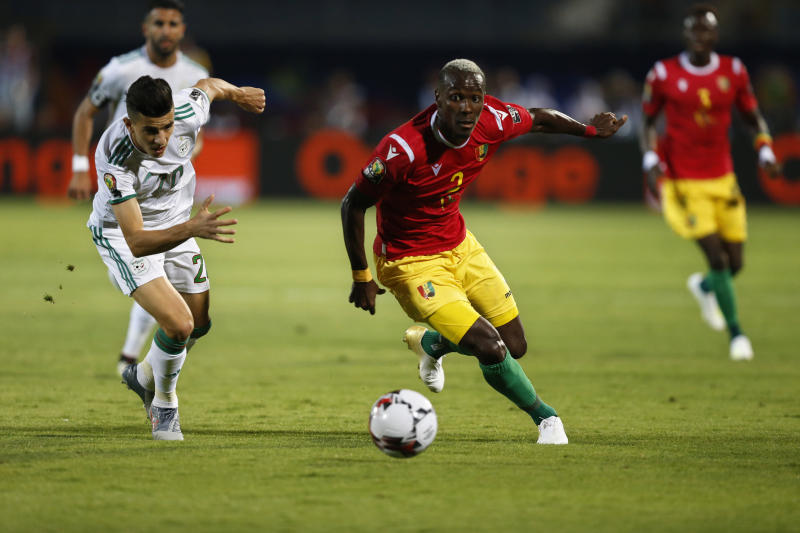 Guinea's Mohamed Yattara and Algeria's Youcef Atal run for the ball during the African Cup of Nations round of 16 soccer match between Guinea and Algeria in 30 June stadium in Cairo, Egypt, Sunday, July 7, 2019. (AP Photo/Ariel Schalit)