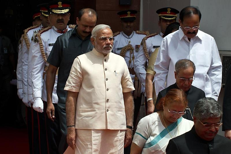 Indian President Pranab Mukherjee (2ndR, in black) arrives with Indian Prime Minster Narendra Modi (front L, in tan) to address the joint session of Parliament in New Delhi on June 9, 2014