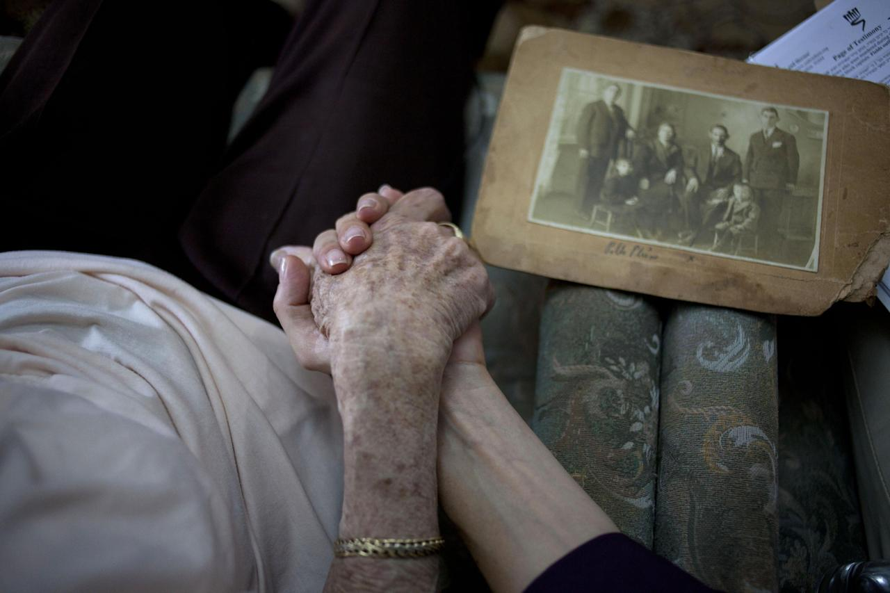 In this photo taken on Sunday, May 5, 2013, Holocaust survivor Rivka Fringeru, 82, left, holds hand with Cynthia Wroclawski, director of Yad Vashem names collection project as they sit in her living room in Rehovot, central Israel. With a hand on her chest and moistness building in her eyes, 82-year-old Rivka Fringeru battled back tears as she reeled off a list of names she has rarely voiced in the past 70 years. First her father, Moshe, then her mother, Hava, and finally her two older brothers, Michael and Yisrael. All perished in the Holocaust after the Harabju family from Dorohoi, Romania was rounded up in 1944 and sent to ghettos and camps. Only Rivka and her brother Marco survived, and like so many others they spent the rest of their lives trying to move on and forget. Now, Yad Vashem, Israel's national Holocaust memorial and museum, is asking them to remember. (AP Photo/Ariel Schalit)