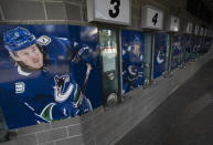 Photos of Vancouver Canucks players are pictured outside the closed box office of Rogers Arena in downtown Vancouver, British Columbia, Thursday, April 8, 2021. The Canucks said Wednesday that 21 players, including three from the taxi squad, and four members of the coaching staff have tested positive in a COVID-19 outbreak. The NHL is in the most difficult position among the four major North American professional sports leagues on vaccinations because seven of its teams are based in Canada. (Jonathan Hayward/The Canadian Press via AP)