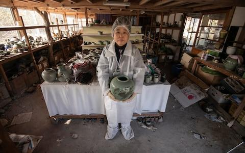 Ceramic artist Keiko Onoda holds up one of her husband Kanjiro's pottery works inside their atelier in Namie, The Onodas fled to Tokyo over radiation fears and have remained there since, occasionally returning to collect their belongings - Credit: Simon Townsley