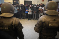 Supporters surround rap singer Pablo Hasél as police officers arrive to arrest him at the University of Lleida, Spain, Tuesday, Feb. 16, 2021. A rapper in Spain and dozens of his supporters have locked themselves inside a university building in the artist's latest attempt to avoid a prison sentence for insulting the monarchy and praising terrorism. (AP Photo/Joan Mateu)