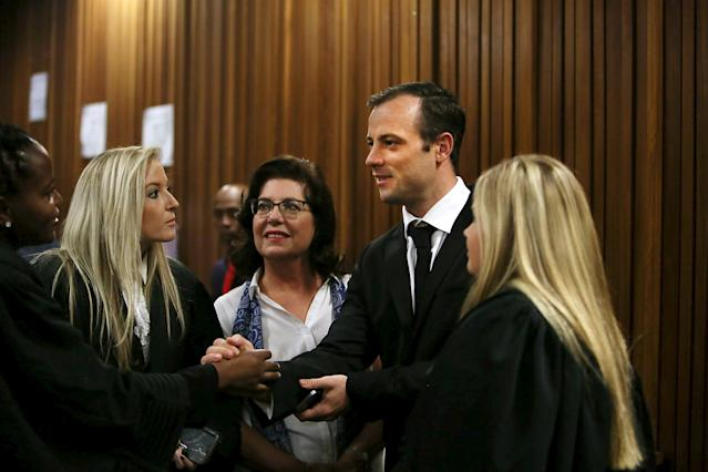 Oscar Pistorius speaks with members of his legal team before appearing for a postponement of sentencing hearing at the High Court in Pretoria, South Africa, April 18, 2016. REUTERS/Alon Skuy/Pool