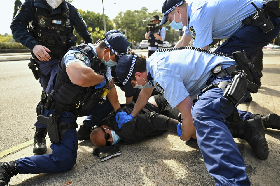 Police arrest a man during an anti-lockdown protest in Sydney, Australia, Saturday, Aug. 21, 2021. Protesters are rallying against government restrictions placed in an effort to reduce the COVID-19 outbreak. (Steven Saphore/AAP Image via AP)