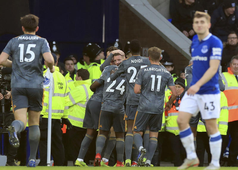 Leicester City's Jamie Vardy looks out as he is mobbed by team-mates after scoring his sides first goal of the game against Everton, during their English Premier League soccer match at Goodison Park in Liverpool, England, Tuesday Jan. 1, 2019. (Peter Byrne/PA via AP)