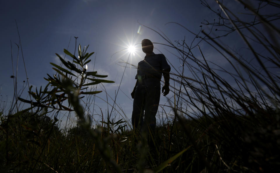 Andy Sansom walks on his property near the site of a proposed new natural gas pipeline would pass through his ranch in the Texas Hill Country near Stonewall, Texas Friday, Aug. 2, 2019. A proposed pipeline is a 430-mile, $2 billion natural gas expressway that pipeline giant Kinder Morgan has mapped from the booming West Texas oil patch to Houston. (AP Photo/Eric Gay)
