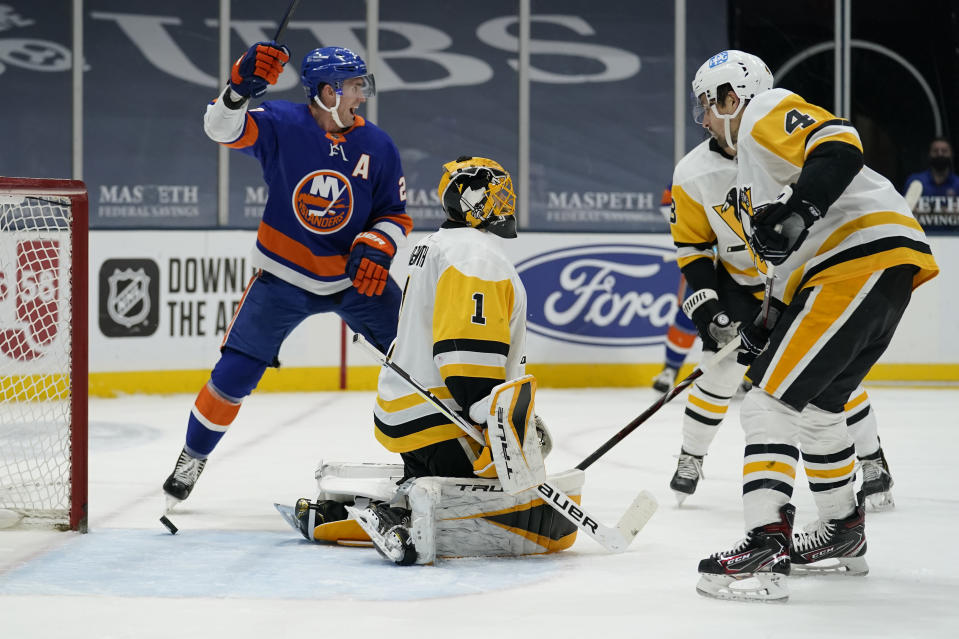 New York Islanders center Brock Nelson (29) reacts after Islanders center Jean-Gabriel Pageau (44) scored a goal against Pittsburgh Penguins goaltender Casey DeSmith (1) during the second period of an NHL hockey game, Sunday, Feb. 28, 2021, in Uniondale, N.Y. Pittsburgh Penguins defenseman Cody Ceci (4) is at right. (AP Photo/Kathy Willens)