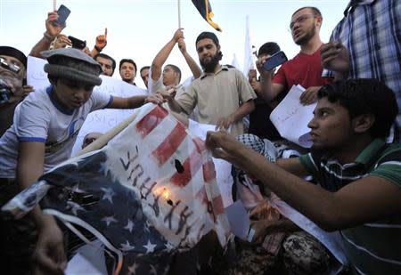 Protesters burn a replica of the U.S. flag during a protest against the capture of Liby in Benghazi