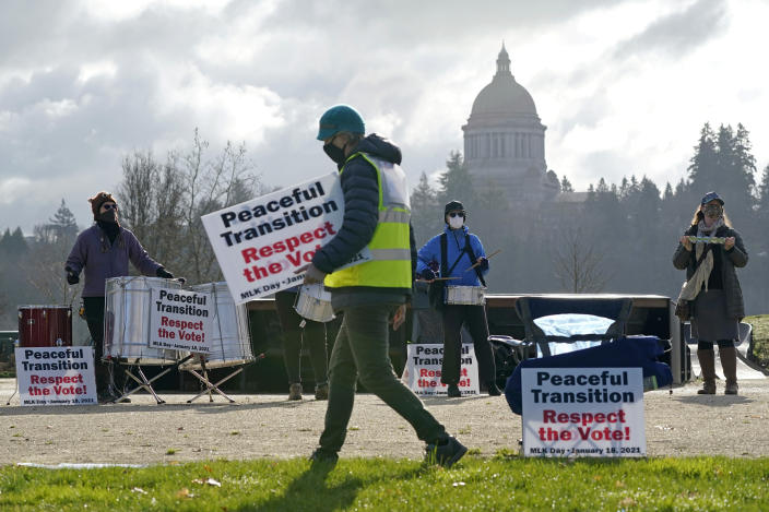 A person walks with a sign near a drum circle during a vigil supporting a peaceful transition from President Donald Trump to President-elect Joe Biden, Monday, Jan. 18, 2021, in Olympia, Wash. More than 100 people took part in the demonstration ahead of Biden's upcoming inauguration on Wednesday. (AP Photo/Ted S. Warren)