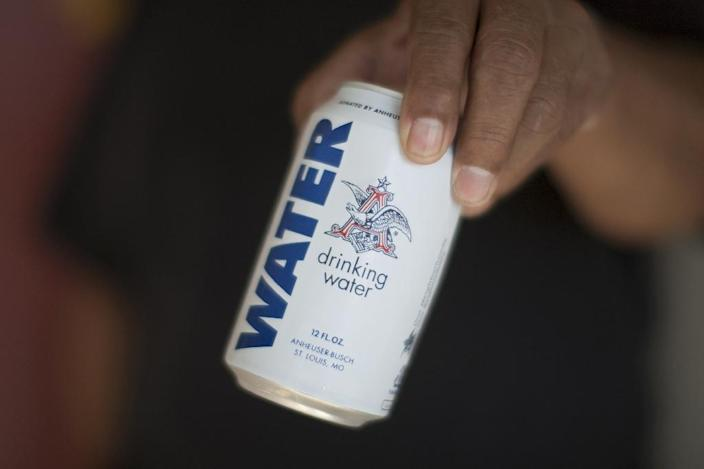 A resident holds a can of water donated by the Anheuser-Busch company as water wells supplying hundreds of residents remain dry in the worsening drought on February 11, 2015 in East Porterville, California (AFP Photo/David Mcnew)