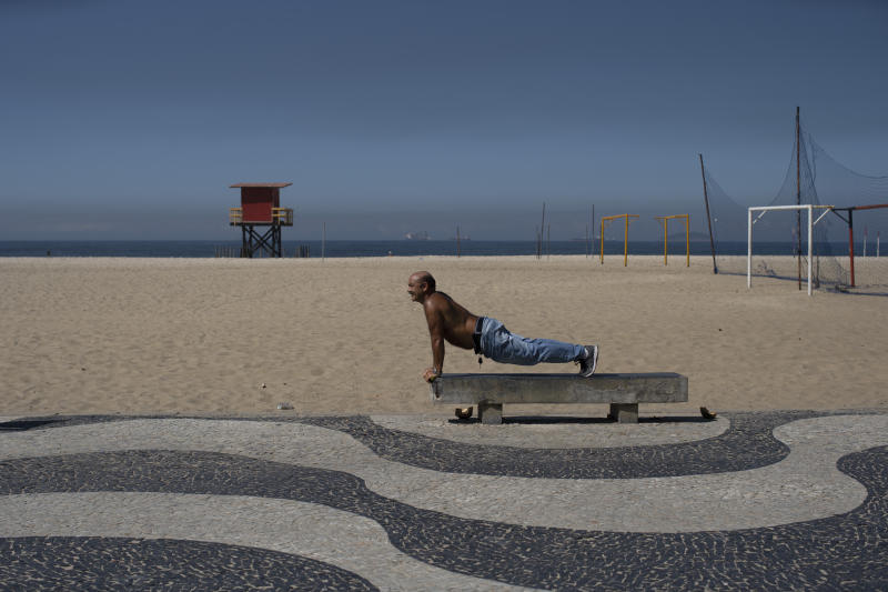 A man exercises on a bench amid the new coronavirus pandemic on Copacabana beach, Rio de Janeiro, Brazil, Wednesday, April 29, 2020. Rejection of quarantine to help contain the spread of COVID-19 is evident among the people soaking up sunshine in the beachside neighborhoods of Copacabana and Barra da Tijuca. (AP Photo/Silvia Izquierdo)