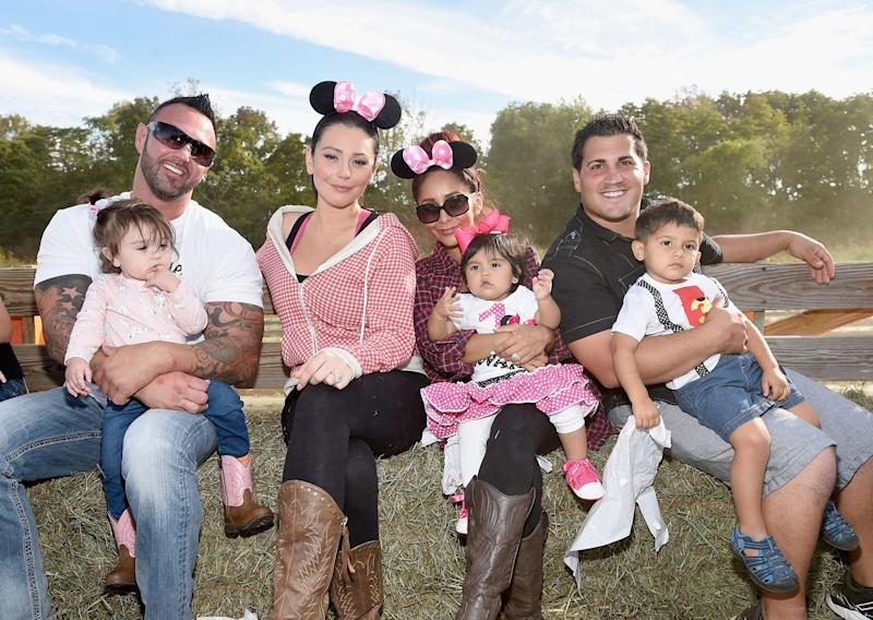 Jenni 'JWoww' Farley and Nicole 'Snooki' Polizzi pose with their spouses and children in September 2015. (Photo: Getty Images)
