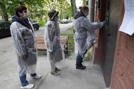 Members of an election commission, wearing gear to protect against coronavirus, enter a residential building as they come to visit a voter who wanted to vote at home during a parliamentary elections in Moscow, Russia, Saturday, Sept. 18, 2021. Sunday, Sept.19 will be the last of three days voting for a new parliament, but there seems to be no expectation that United Russia, the party devoted to President Vladimir Putin, will lose its dominance in the State Duma. (AP Photo/Pavel Golovkin)