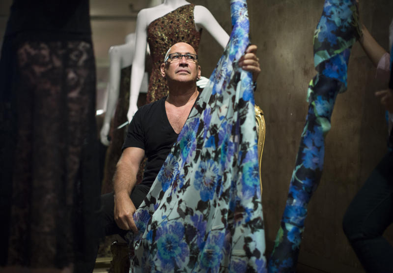 """In this Aug 19, 2013 photo, fashion designer Carmen Marc Valvo sits with a bolt of fabric in his New York studio while putting together his Spring 2014 collection for a Fashion Week runway show on Sept. 6 at Lincoln Center in New York. Valvo has been at this for more than 20 years and says, """"the most rewarding part of building the collection is when you make your final edit and the run of show is set in stone and no more changes can be made."""" (AP Photo/John Minchillo)"""