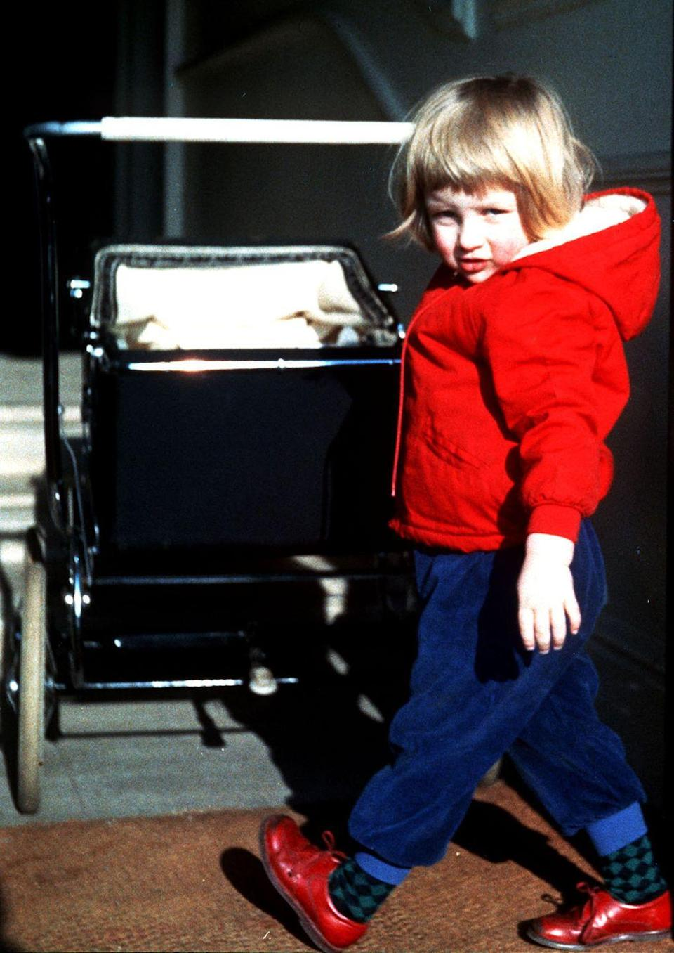 <p>A young Diana plays with a pram stroller, while bundled up at the Spencer family home in a red puffer jacket and loafers. </p>