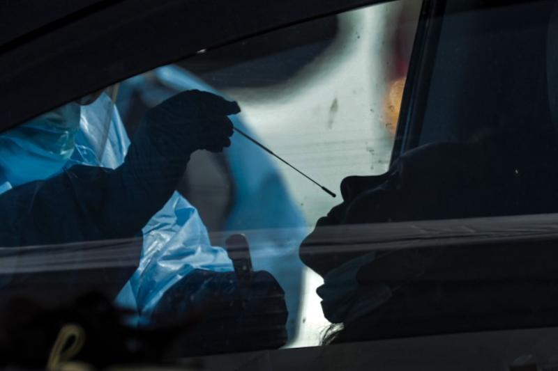 VICTORVILLE, CA - APRIL 02, 2020 - San Bernardino County health care worker takes a sample at a coronavirus COVID-19 drive-thru sample collection that took place at the county fairgrounds on Thursday April 02, 2020, Victorville. ( please keep the image dark / silhouetted to protect the privacy of the patient) (Irfan Khan / Los Angeles Times)