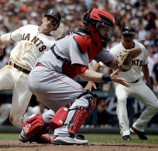 San Francisco Giants' Ryan Theriot, left, slides to score as Cincinnati Reds catcher Ryan Hannigan waits for the ball in the fifth inning of a baseball game, Sunday, July 1, 2012, in San Francisco. Theriot scored on a double from Melky Cabrera. (AP Photo/Ben Margot)