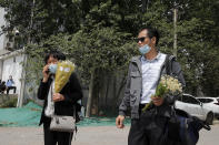 Wei Xiuwen, left, mother of Chen Mei, and Cai Jianli, father of Cai Wei, leave a courthouse after attending their children's court cases in Beijing, Tuesday, May 11, 2021. Two amateur computer coders taken by police from their Beijing homes last year were standing trial Tuesday in a case that illustrates the Chinese government's growing online censorship and heightened sensitivity to any deviation from the official narrative on its COVID-19 response. (AP Photo/Andy Wong)