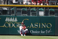 St. Louis Cardinals left fielder Marcell Ozuna sits at the base of the left field wall after failing to catch a solo home run off the bat of Colorado Rockies' Nolan Arenado in the third inning of a baseball game Thursday, Sept. 12, 2019, in Denver. (AP Photo/David Zalubowski)