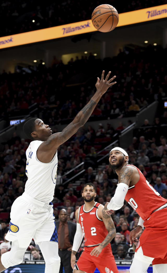 Indiana Pacers guard Edmond Sumner, left, drives to the basket on Portland Trail Blazers forward Carmelo Anthony, right, as guard Gary Trent Jr., center, looks on during the first half of an NBA basketball game in Portland, Ore., Sunday, Jan. 26, 2020. (AP Photo/Steve Dykes)