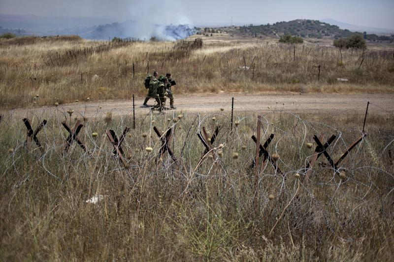 Israeli soldiers walk back from a position on the border with Syria on the Israeli controlled Golan Heights as smoke rises following explosions, Tuesday, July 16, 2013. Three mortar shells exploded on the Israeli side of the border fence with Syria on the Golan Heights Tuesday morning. No casualties or damage were reported from the incident, and there are currently no special security instructions for residents of the area. The shells fell at 6 a.m. local time, and the IDF was combing the area to collect any residual material from the exploded ordinance, the IDF Spokesperson's Unit said. According to the IDF, the fire was not directed at Israel, but was fired as part of the battle currently raging in the nearby Syrian village of Al-Madriya, where rebels are clashing with regime forces. (AP Photo/Ariel Schalit)